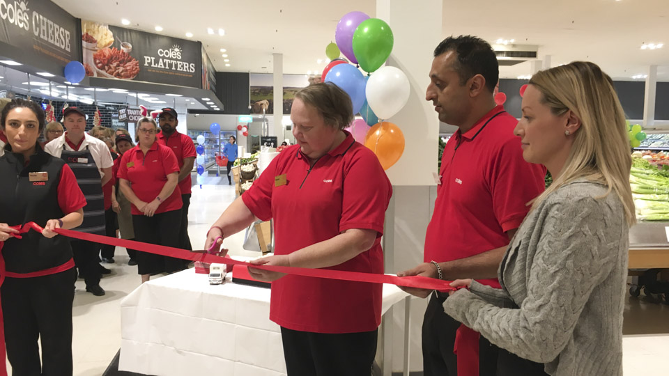 Coles employee Karen Waver reopens the Oakleigh store with a ribbon cutting ceremony.